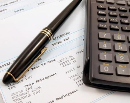 A payslip with a calculator and pen