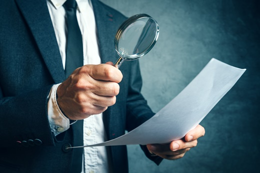 Tax inspector investigating financial documents through magnifying glass