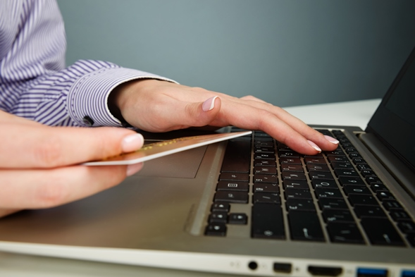 hands holding a credit card and using computer keyboard for online shopping